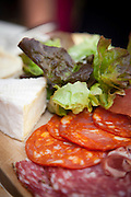 A lunch of cheeses and meat at a brasserie in the Belleville district of Paris, France