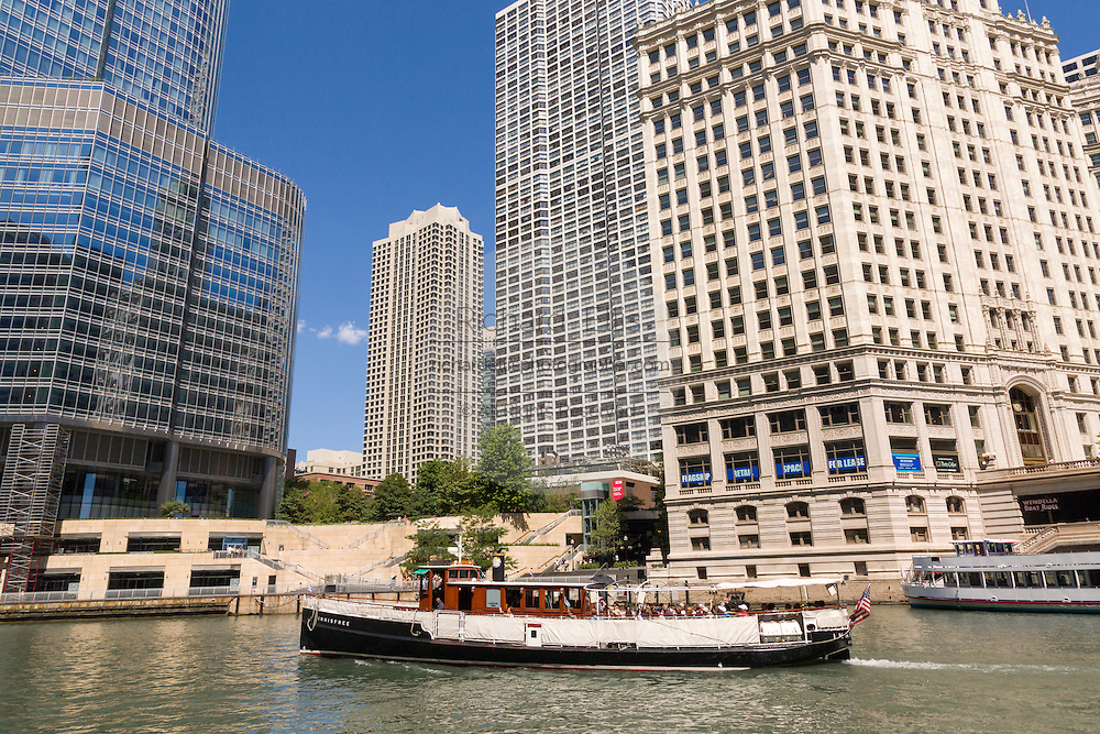 A boat tour travels down the Chicago River past the Wrigley Building on a summers day in Chicago, Illinois, USA