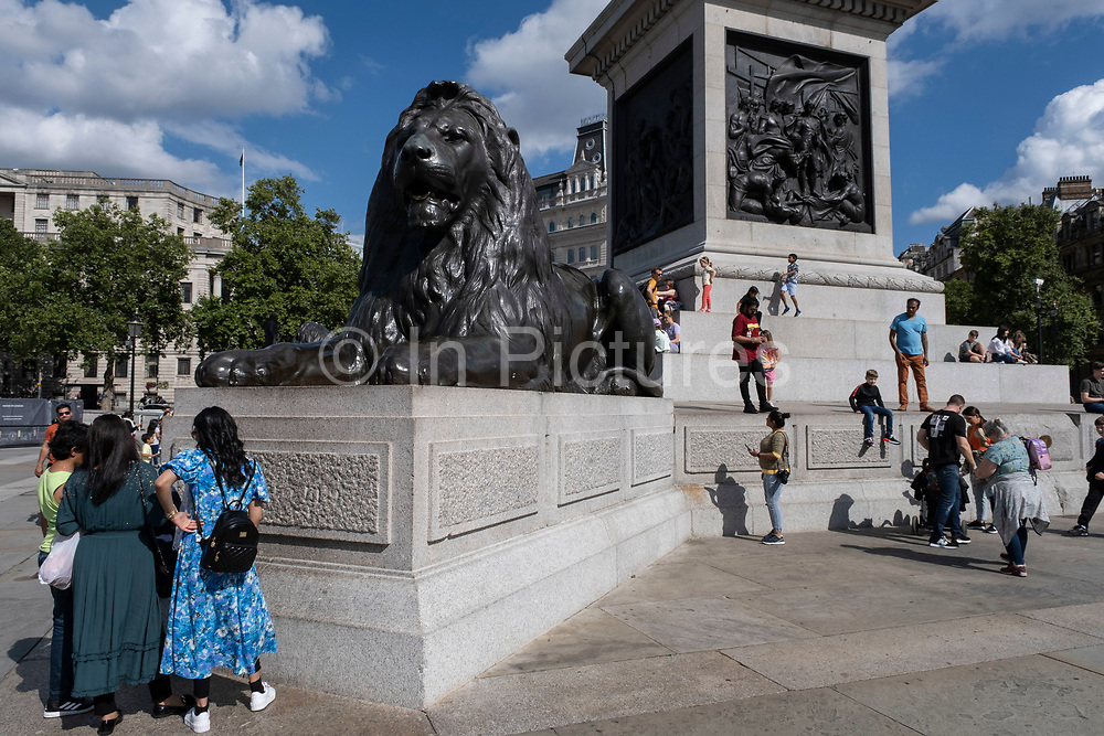 With many people and families staying in the UK for their Summer break during the school holidays, a large number of domestic tourists, who may normally have been travelling abroad, have decended on the capital to see the sights, as seen here having fun climbing the lions at the base of Nelsons Column in Trafalgar Square on 10th August 2021 in London, United Kingdom. Following the Coronavirus / Covid-19 health scare of the last two years, and with some travel restrictions still in place, more people have chosen a staycation which is a holiday spent in ones home country rather than abroad, or one spent at home and involving day trips to local attractions.