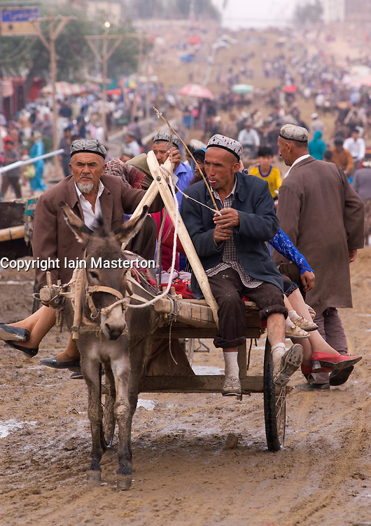 People travelling on donkey cart to famous Kashgar Sunday market in Xinjiang Province China