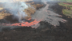 """July 3, 2018 - Hawaii, U.S. - Evolution of a blocked channel, image 2: While observing this area of the fissure 8 lava channel near Kapoho cone during the morning overflight, geologists witnesed an """"apartment-building-sized"""" blockage within the channel give way and be pushed down stream by the pressurized lava behind. The dark portion within the red channel is the freed blockage. Lava continues to overflow behind the bend and form a cooled black crust. The more quickly flowing lava at the bend has very little crust (Credit Image: © USGS/ZUMA Wire/ZUMAPRESS.com)"""