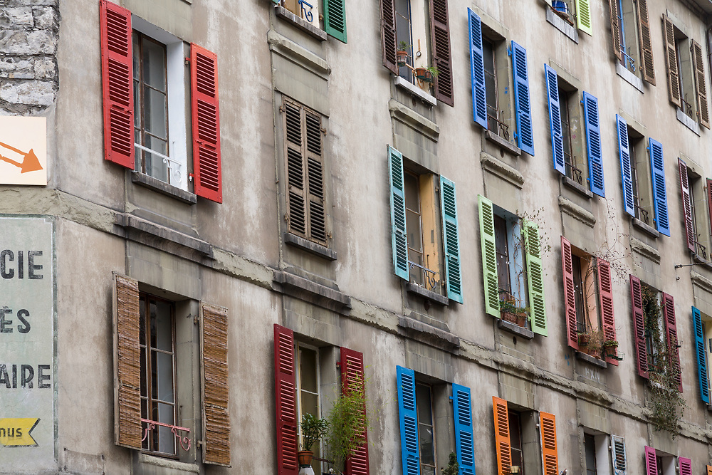Multi Colored window shutters adorn an old dreary tenement building with a little cheer in the Swiss city of Geneva.  Licensing and Open Edition Prints.
