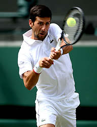 Novak Djokovic in action against Philipp Kohlschreiber on day one of the Wimbledon Championships at the All England Lawn Tennis and Croquet Club, Wimbledon.