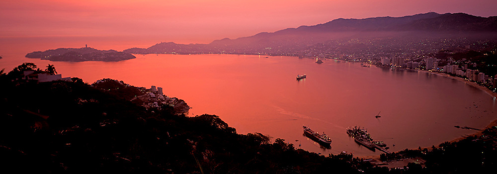 MEXICO, PACIFIC COAST, GUERRERO STATE ACAPULCO; the Bay of Acapulco with the Isla de la Roqueta at the bay entrance at sunset