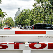 A road barricade with STOP painted on it on one of the approach streets to the US Capitol building, the dome of which is visible in the distance.