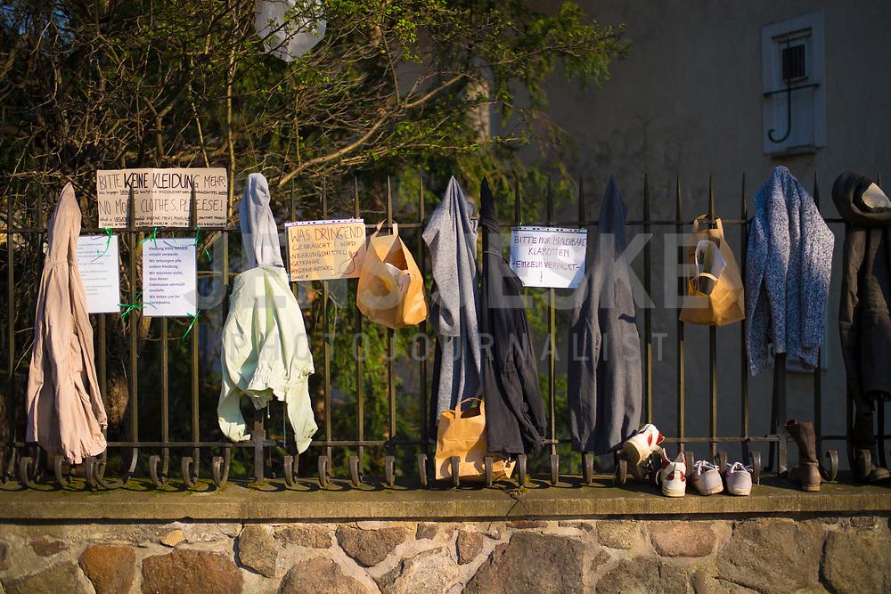 DEU, Deutschland, Germany, Berlin, 08.04.2020: Anwohner spenden Kleider und Schuhe für Bedürftige und Obdachlose an einem Gabenzaun im Bezirk Neukölln. Auswirkungen der Pandemie, Coronavirus (Covid-19), Corona auf das öffentliche Leben in Berlin.