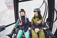 Sammy Podhurst and Janelle Huelsman fuel up on the gondola before a day of powder skiing on Aspen Mountain, Colorado.