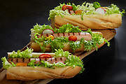 Sub sandwiches with grilled wurst, salad, tomatoes and radish.<br /> Sold exclusively through Stockfood.com