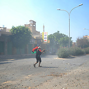 A rebel fighter aims at pro-Gaddafi snippers during the third day of street-to-street battle for control of the strategically coastal city of Zawiyah.