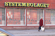 The front of one of the Systembolaget shops, the retail monopoly for selling alcohol wine beer and spirits, with a yellow neon sign and the iron wire curtain closed on Soder in the shopping centre Ringen A lone woman walking by carrying plastic shopping bags. Stockholm, Sweden, Sverige, Europe