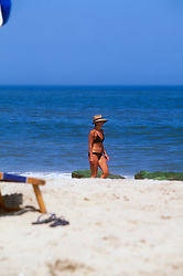 An unidentified woman walks along the strand, Friday, Aug. 16, 2019 at Henlopen Acres Beach Club in Rehoboth Beach, Del. (Photo by D. Ross Cameron)
