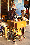 Africa, Tanzania, Lake Eyasi National Park Adult Hadzabe male at a foot operated sewing machine April 2007