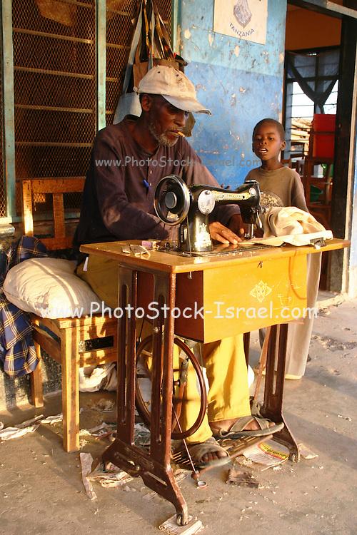 Africa, Tanzania, Lake Eyasi National Park Adult Hadzabe male at a foot operated sewing machine April 2007