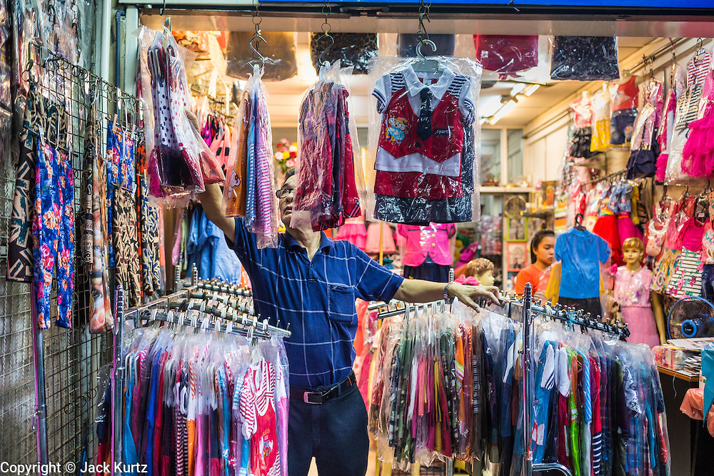 06 JUNE 2013 - BANGKOK, THAILAND:     A clothing vendor sets up his shop in Bobae Market in Bangkok. Bobae Market is a 30 year old market famous for fashion wholesale and is now very popular with exporters from around the world. Bobae Tower is next to the market and  advertises itself as having 1,300 stalls under one roof and claims to be the largest garment wholesale center in Thailand.       PHOTO BY JACK KURTZ
