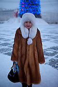 Portrait of a Yakutian woman wearing fur clothes in the streets of Yakutsk. Yakutsk is a city in the Russian Far East, located about 4 degrees  (450 kilometres) south of the Arctic Circle. It is the capital of the Sakha (Yakutia) Republic in Russia with a major port on the Lena River. The city has a population of 264.000 (2009). Yakutsk is one of the coldest cities on Earth. The average monthly winter temperature in January is around -43,2 C. Yakutsk, Jakutsk, Yakutia, Russian Federation, Russia, RUS, 16.01.2010.