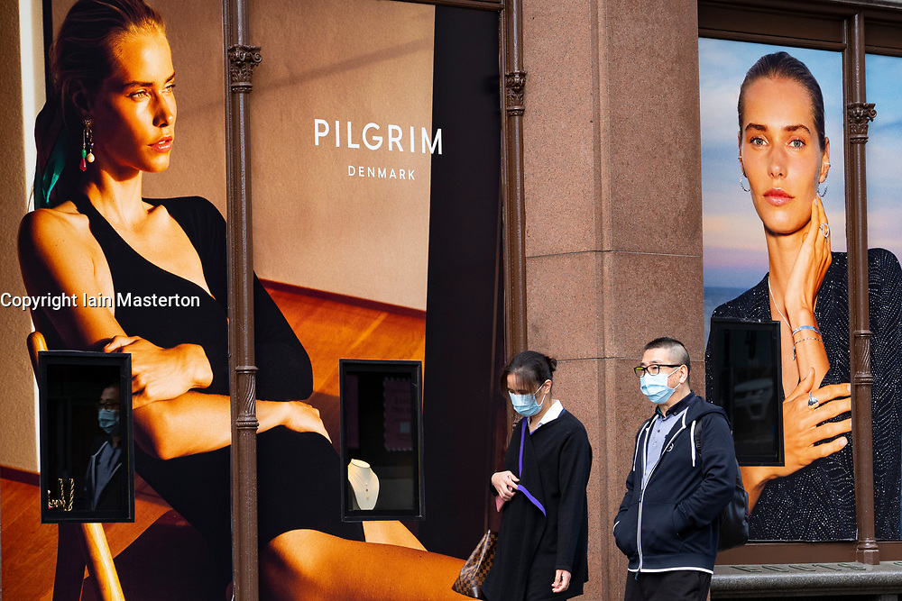 Edinburgh, Scotland, UK. 28 July, 2020. Business and tourism slowly returning to the shops and streets of Edinburgh city centre. A couple wearing facemarks walk past shop window advertising display in Jenners department store. The retail industry is suffering severe problems with many job losses. Iain Masterton/Alamy Live News