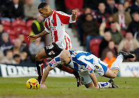 Photo: Leigh Quinnell.<br /> Brentford v Huddersfield Town. Coca Cola League 1. 21/01/2006. Brentfords Dudley Campbell leaves Huddersfields Danny Adams on the floor.