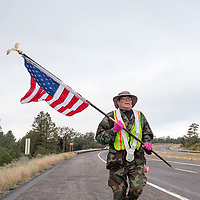 Kirk Mitchell. 49, runs down AZ-264 carrying the American flag, along with others, makes his way to the Navajo Nation Council Chambers in Window Rock on Wednesday.