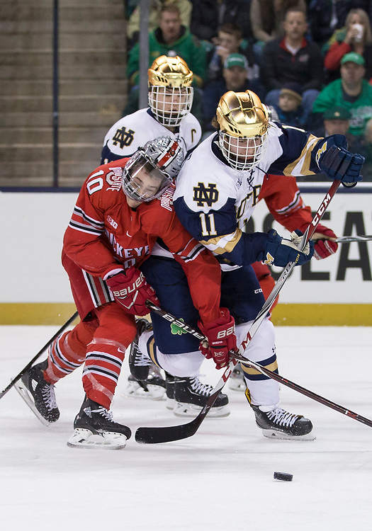 March 17, 2018:  Notre Dame forward Cal Burke (11) and Ohio State forward John Wiitala (10) battle for the puck during NCAA Hockey game action between the Notre Dame Fighting Irish and the Ohio State Buckeyes at Compton Family Ice Arena in South Bend, Indiana.  Notre Dame defeated Ohio State 3-2 in overtime.  John Mersits/CSM