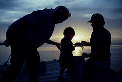 Stock photo of a man and woman at the gulf crabbing with their young son at sunset