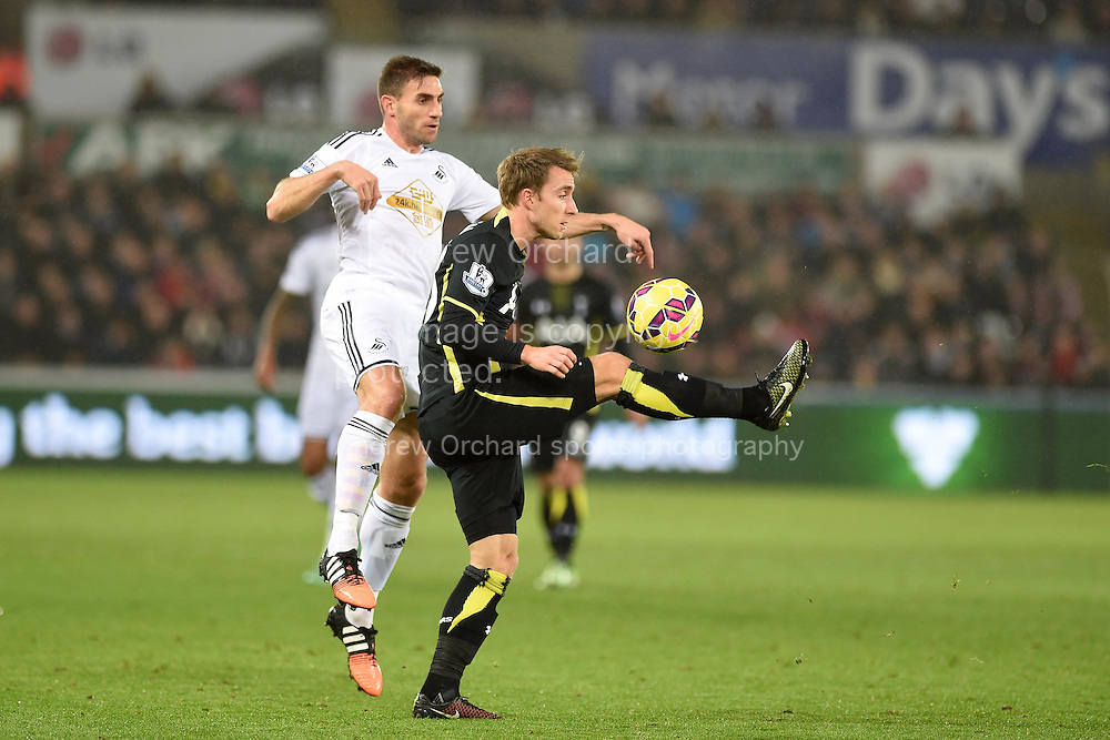 Christian Eriksen of Tottenham is challenged by Swansea's Angel Rangel. Barclays Premier League match, Swansea city v Tottenham Hotspur at the Liberty Stadium in Swansea, South Wales on Sunday 14th December 2014<br /> pic by Andrew Orchard, Andrew Orchard sports photography.