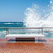 An expansive and sunny promenade on the city sea front at Las Palmas in Gran Canaria. Lots of lovely wide seats so sit on whilst enjoying the view of the Atlantic Ocean waves.<br />