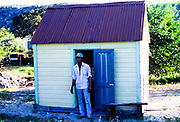 Young man standing outside small shed building, Cayman Brac, Cayman Islands, West Indies c 1990
