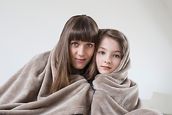 Portrait of mother and daughter covered with blanket, smiling