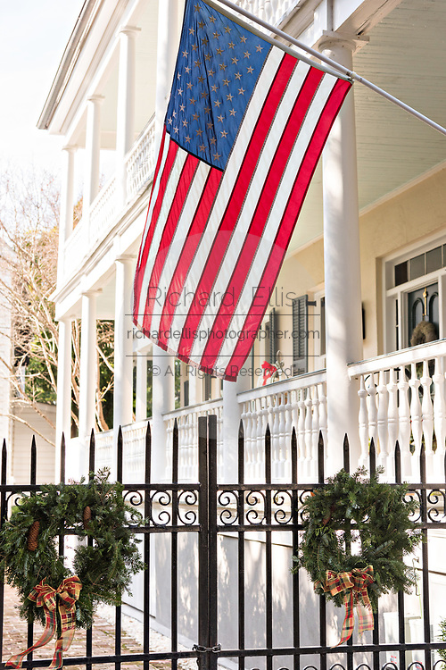 An American flag hangs above Christmas wreaths on the wrought iron gate of a historic home on Church Street in Charleston, SC.