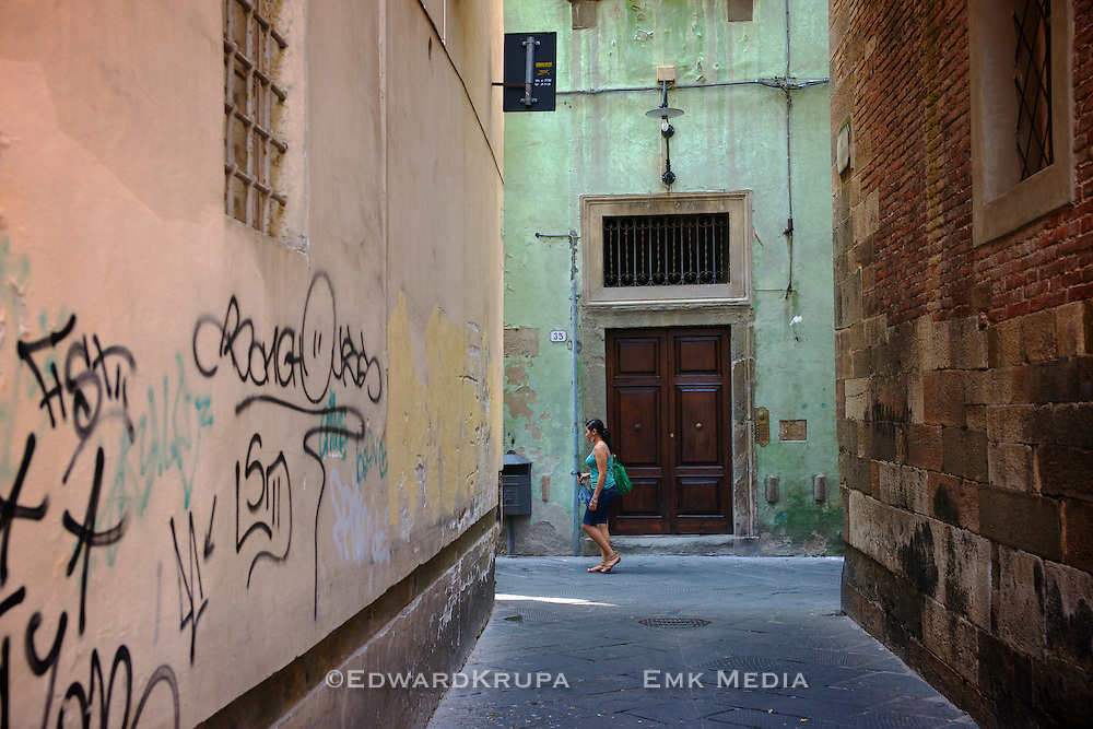 A woman walks along a medieval street in Lucca, Tuscany Italy.
