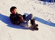 Boy body sledding on small hill during March in the village of Nikolai, Alaska.