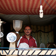 August 08, 2013 - Zaatari, Jordan: A shisha vendor stands at his stall in Zaatari refugee camp in northern Jordan. The stall is located on a street that aid workers have nicknamed the Champs Elysees, due to the hundreds of shops and businesses. Zaatari camp, home to more than 120,000 people who in the past year have fled the conflict in Syria, become the fourth largest city in Jordan and the world's second largest refugee camp behind Dadaab in eastern Kenya. Most of its residents came from Daraa, a city about 30Km away in Syria, rich with businessmen thanks to a long history of cross-border trade with Jordan. (Paulo Nunes dos Santos/Al Jazeera)