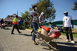 South Africa  - Johannesburg -  Olievenhoutbosch relief program business opportunity. Following a reported 3 km queue for food relief hampers in Olieven as it is affectionately known by the people of ext 21, of this Midrand Township new opportunities presented themselves and the youth of the area are grabbing them. When people receive the Covid-19 food parcels provided by various organisations, the recipients are often overwhelmed by the size of the hamper and cannot carry it home. Four youth from the area saw the need and gathered a group of 30 youngsters with wheelbarrows to render a service of delivering the parcels at a cost of up to R30 depending on distance.  They call themselves the Wheelbarrow association and operating from the Steve Tshwete Secondary school they accompany the beneficiary home to deliver the parcel containing 12.5kg  Maze meal. 10kg rice, 10kg flower, 10 Kg mielie rice and other groceries.   <br /> Picture: Timothy Bernard/ African news Agency(ANA)