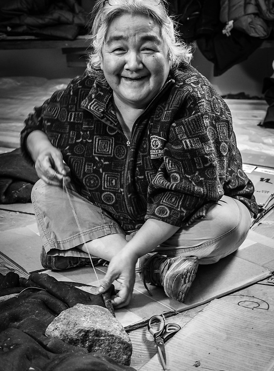 Alicie Kasadluak, sewing a seal skin that will be used to cover an umiak (women boat).