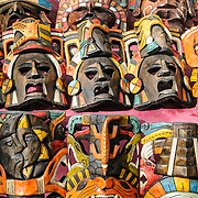 Market stalls selling wooden Mayan masks and other local souvenirs and handicrafts to tourists visiting Chichen Itza Mayan ruins archeological site in Mexico.