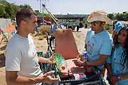 Mario Van Peebles (from the television series Mario's Greenhouse) talks to Marcus Eriksen of Algalita about the plastic bottle kayak that Marcus is displaying at the FoLAR (Friends of the LA River)  clean-up at the Glendale Narrows. Los Angeles, California, USA
