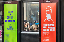© Licensed to London News Pictures. 06/01/2021. London, UK. Members of the public wait at a bus stop displaying Covid-19 information in Chelsea, South West London as cases continue to rise dramatically throughout the capital with the UK recording over 60,000 positive tests a day. Yesterday, Prime Minister Boris Johnson plunged England into another lockdown as he ordered schools to close and office workers to work from home in his televised address to the nation. This week, the first person in the world was vaccinated with the Oxford AstraZeneca Covid-19 vaccine with over 500,000 doses made available for high risk groups as the government race to vaccinate 13 million people in seven weeks. Photo credit: Alex Lentati/LNP