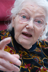 Woman with Alzheimer's disease pointing whilst chatting,