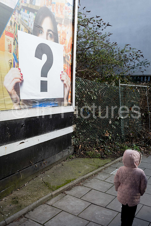 A south London child walks beneath a question mark being held in the context of a billboard ad, on 10th February 2019, in London, England.