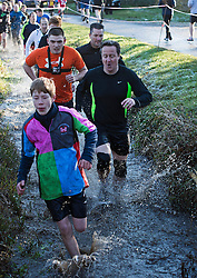 © Licensed to London News Pictures. British Prime Minister DAVID CAMERON taking part in The Great Brook Run in Chadlington, Oxfordshire on December 29, 2014. The cross-country course, which is over a mile long, takes competitors through muddy fields, through cold water and under 3-foot wide tunnel. Photo credit : Ben Cawthra/LNP