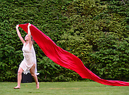 Old Westbury, New York, U.S. 22nd June 2013. Dancer in white in Lori Belilove & The Isadora Duncan Dance Company, holds a long red flowing cloth over her head during a dance at the Midsummer Night event at Old Westbury Gardens, on the grounds of the historic Long Island Gold Coast estate.