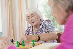 Senior women playing board game in rest home, Bavaria, Germany