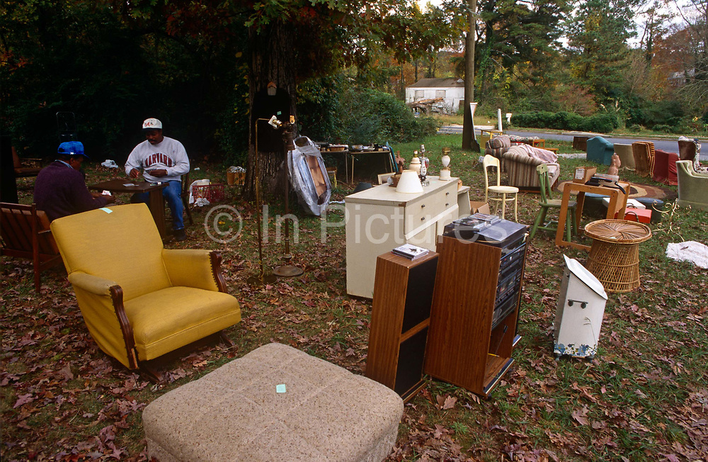 Two Georgian men play cards while waiting for passing trade during an outdoor yard sale in an Atlanta suburb. The male friends sit on old chairs at a table surrounded by furniture from a nearby home. Chairs, units, cabinets, sofa seats, and music centres sit on the ground on which autumn leaves still lie on roadside grass. Perhaps out of economic necessity or merely to clear space in someone's home, the possessions need to be sold to passers-by, drivers on a road in this suburb of Atlanta, Georgia.