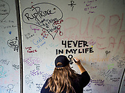 21 APRIL 2017 - CHANHASSEN, MN: A woman writes a note to Prince in the pedestrian tunnel in front of Paisley Park, his former home and recording studio. The tunnel has become a memorial to Prince, people have drawn graffiti in the tunnel honoring him and they leave memorials in the tunnel. The superstar died from an accidental overdose of the opioid fentanyl on April 21, 2016. Friday was the first anniversary of his death. Crowds of people gathered at Paisley Park, which is now a museum, to honor the Minnesota born musician.     PHOTO BY JACK KURTZ