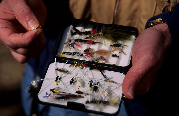 Stock photo of a man holding a box full of fly fishing lures