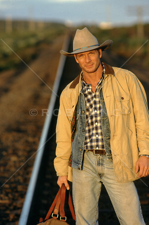 cowboy standing by railroad tracks
