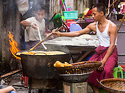 02 NOVEMBER 2014 - YANGON, MYANMAR: A vendor makes fried Burmese bread sticks in the 38th Street morning market in downtown Yangon, Myanmar. The market is typical of morning markets in Yangon, a city coming out of more the 50 years of economic isolation. Most people still shop in markets because Yangon does not have as many grocery stores as Bangkok, Kuala Lumpur or many other large cities.     PHOTO BY JACK KURTZ