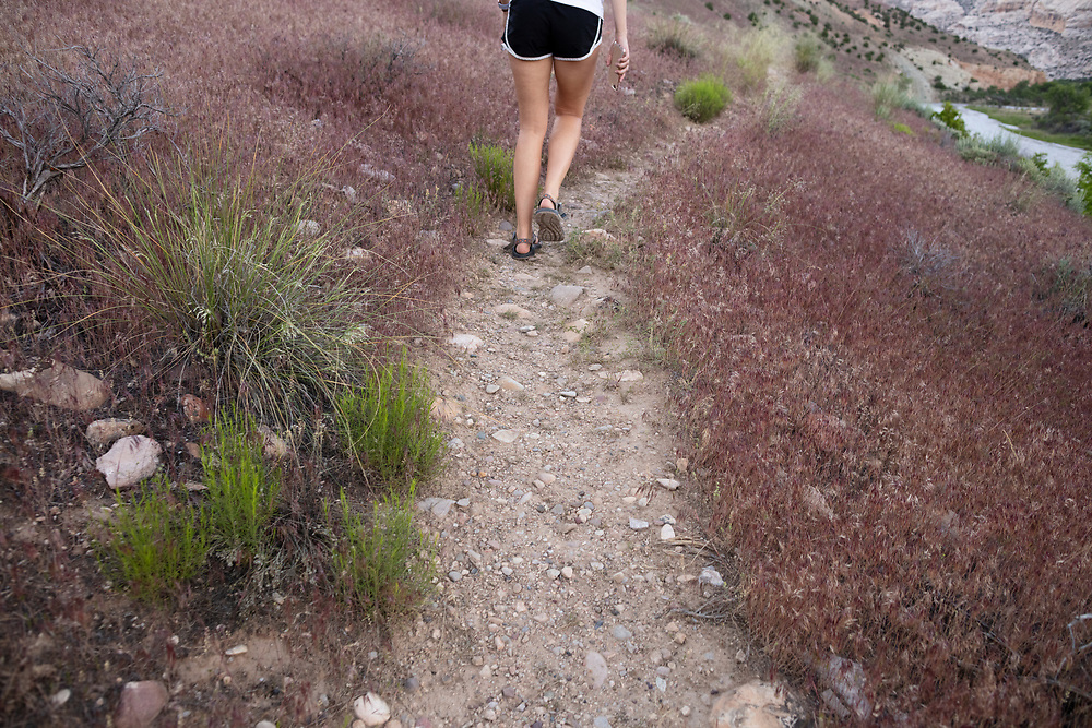 young woman walking on the River trail in DInosaur National Monument from behind with a cell phone in her hand