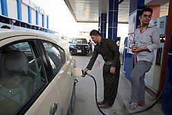 i© Licensed to London News Pictures. 26/06/2014. Sulaimaniyah, Iraq. Iraqi drivers fill their tanks at a petrol station in Sulaimaniyah, Iraqi-Kurdistan. Despite being an oil-rich country Iraq's main oil refinery at Baiji is now the hands of ISIS insurgents cutting much of the fuel to the rest of the country. Petrol rationing has come in to force across northern Iraq with huge queues that mean many drivers wait in line for hours, sometimes overnight, just to receive their allowance of 30 litres. The shortage has also seen a huge increase in fuel prices with a litre of petrol rising 150% from 500 Iraqi Dinars to 1500 Iraqi Dinars. Photo credit: Matt Cetti-Roberts/LNP