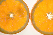 Cutout of a back lit slices of orange on white background